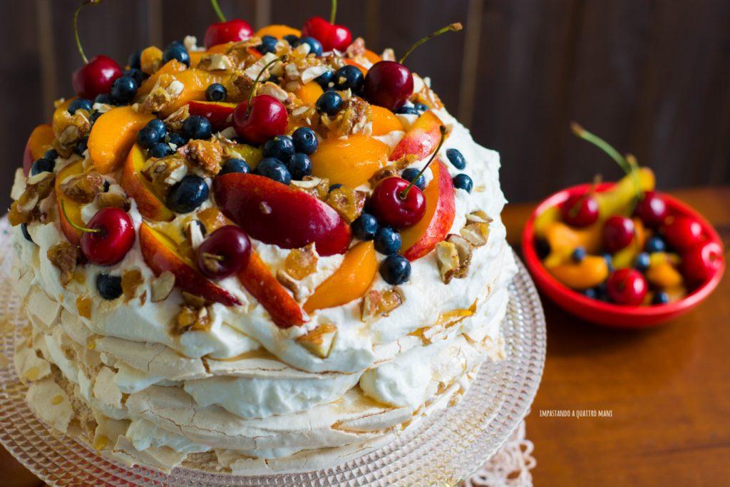 pavlova con meringa alla cannella, frutta fresca, panna, sciroppo d'acero e pralinato alle mandorle, dolce australiano